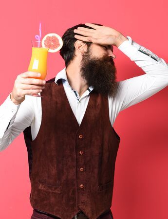 handsome bearded man with long beard and mustache has stylish hair on disappoint face holding glass of alcoholic cocktail in vintage suede leather waistcoat on red studio background Stock Photo