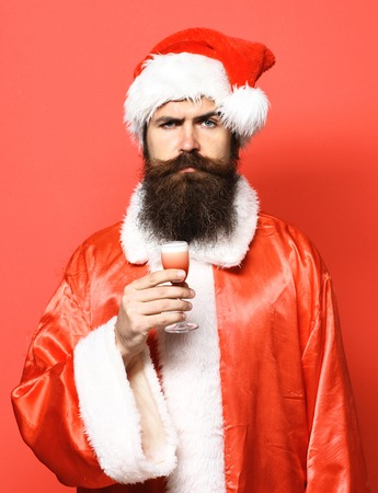 handsome bearded santa claus man with long beard on serious face holding glass of alcoholic shot in christmas or xmas sweater and new year hat on red studio background