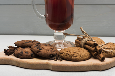 vin chaud: Glass of delicious glintwein or mulled hot wine on cutting board with cinnamon, thread, anise and oatmeal cookies on vintage wooden background