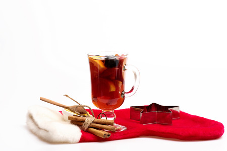 vin chaud: Glass of delicious glintwein or mulled hot wine honey, wooden spoon, cinnamon, silver star and Santa Claus red sock isolated on white background, side view