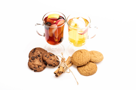 vin chaud: Two glasses of delicious glintwein or mulled red and white hot wine, cinnamon and oatmeal cookies isolated on white background