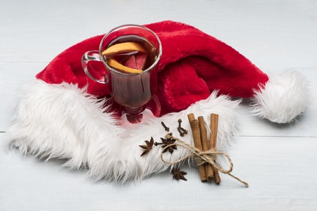 vin chaud: Glass of delicious glintwein or mulled hot wine, cinnamon, thread, anise and Santa Claus red hat on vintage wooden background