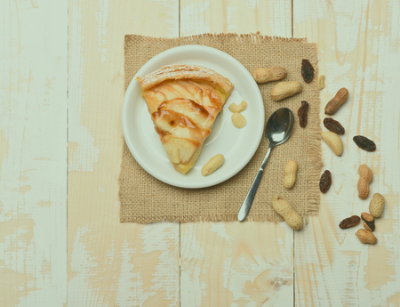 servilleta de papel: Single slice of apple pie with peanuts, raisins, white plate, spoon and knitted serviette on vintage wooden background