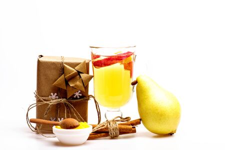 vin chaud: Glass of delicious glintwein or mulled hot wine, cinnamon, honey, wooden spoon, pear, gift wrapped in craft paper with bow and snowflakes isolated on white background, side view