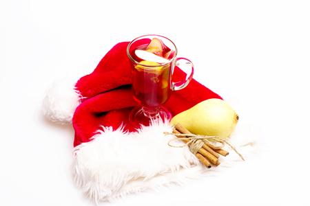 vin chaud: Un verre de délicieux glintwein ou vin chaud, de cannelle et de poire avec le Père Noël chapeau rouge isolé sur fond blanc