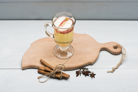 vin chaud: Glass of delicious glintwein or mulled hot wine on cutting board with cinnamon, thread and anise on vintage wooden background