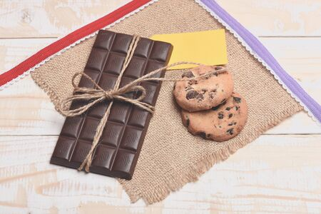servilleta de papel: Dark chocolate bar with thread, oatmeal chocolate cookies, yellow tag, knitted serviette and red, purple ribbons on vintage wooden background