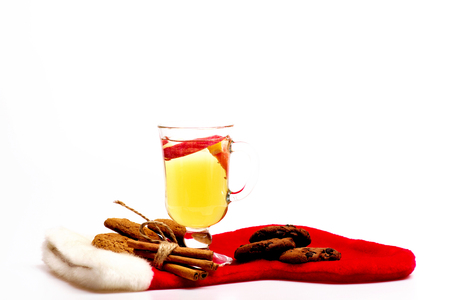 vin chaud: Glass of delicious glintwein or mulled hot wine, cinnamon and oatmeal cookies with Santa Claus red sock isolated on white background, side view Banque d'images