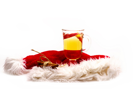 Glass of delicious glintwein or mulled hot wine, cinnamon with Santa Claus red hat isolated on white background