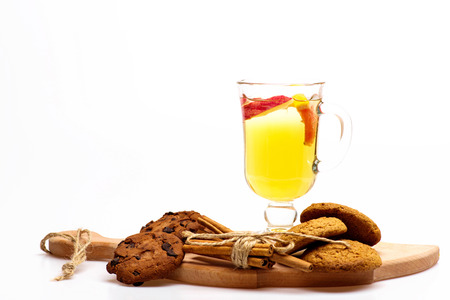 vin chaud: Glass of delicious glintwein or mulled hot wine on cutting board with thread, cinnamon, walnuts and oatmeal cookies isolated on white background