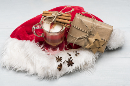 wine gift: Glass of delicious glintwein or mulled hot wine, gift wrapped in craft paper with bow, cinnamon, thread, anise and Santa Claus red hat on vintage wooden background Stock Photo