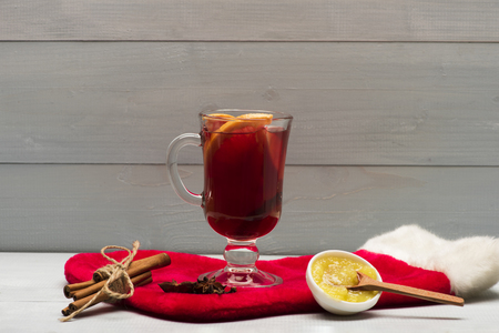vin chaud: Glass of delicious glintwein or mulled hot wine, honey, wooden spoon, anise and Santa Claus red sock on vintage wooden background