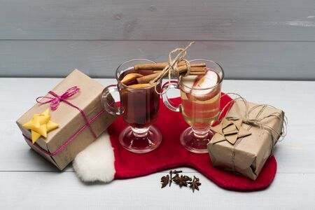 vin chaud: Two glasses of delicious glintwein or mulled red and white hot wine, cinnamon, thread, anise, gifts wrapped in craft paper with bow and with Santa Claus red sock on vintage wooden background Banque d'images
