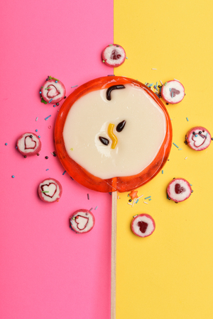 Set of l lollipop as red apple and candies with valentine heart sign and sprinkles on colorful background, top view