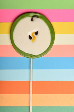 Lollipop as green apple on colorful background, top view