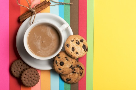 string top: White cup of coffee with milk on plate, cinnamon with string and chocolate chip cookies on colorful rainbow background, top view
