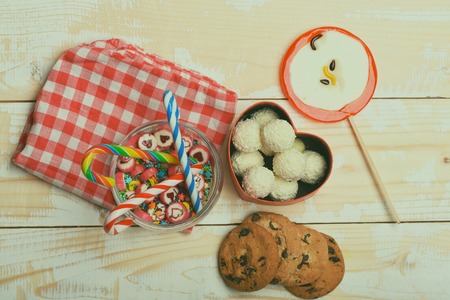 Chocolate chip cookies, coconut candies in valentine gift box, lollipop as red apple, striped and caramel candies with sprinkles in glass jar on checkered pink napkin on vintage wooden background