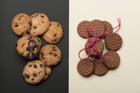 string top: Chocolate chip cookies tied with pink and rainbow string placed on opposite sides on black white background, top view