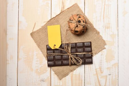 servilleta de papel: Dark chocolate bar with thread, oatmeal chocolate cookies, yellow tag and knitted serviette on vintage wooden background