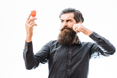 handsome bearded man with stylish hair mustache and long beard on enthusiastic face holding glass of red alcoholic beverage isolated on white