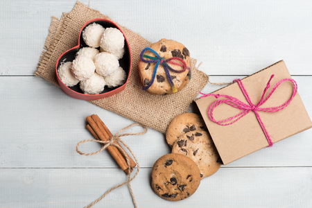 string top: Chocolate chip cookies tied with rainbow string, white coconut candies in valentine gift box, cinnamon, gift with pink thread with sacking napkin on vintage wooden background, top view Stock Photo