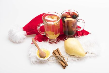 vin chaud: Two glasses of delicious glintwein or mulled red and white hot wine, cinnamon, pear, honey, wooden spoon and Santa Claus red hat isolated on white background