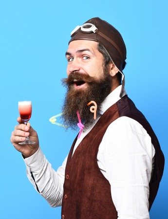 handsome bearded pilot or aviator man with long beard and mustache on smiling face holding glass of alcoholic shot in vintage suede leather waistcoat with hat and glasses on blue studio background Stock Photo