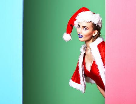 pretty cute sexy santa girl or smiling blonde woman with fashion blue lips in new year swimsuit and christmas hat or xmas cape on colorful studio background, copy space Stockfoto