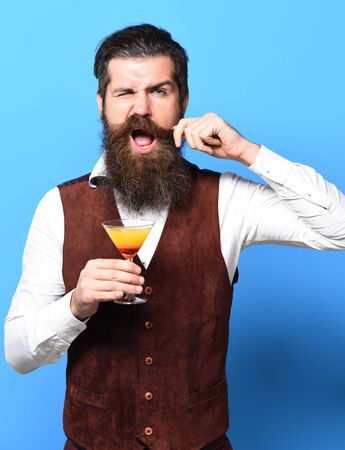 handsome bearded man with long beard and mustache has stylish hair on funny face holding glass of alcoholic cocktail in vintage suede leather waistcoat on blue studio background