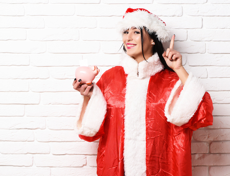pretty cute sexy santa girl or smiling brunette woman in new year sweater and christmas or xmas hat holds pink piggy pig bank with raised finger on white brick wall background