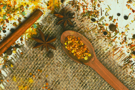 spiciness: set of ingredients for cooking spicy fragrant spices in spoons with cinnamon and chili pepper on net sacking and vintage wooden background, top view Stock Photo