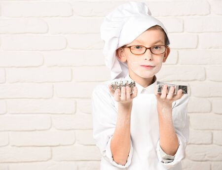 young boy small cute cook chef in white uniform and hat on stained face flour with glasses holding cookie cutter stars on brick wall background, copy space Stock Photo