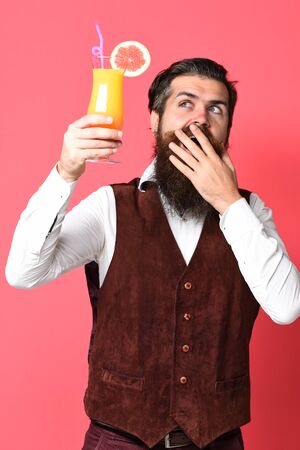 handsome bearded man with long beard and mustache has stylish hair on surprised face holding glass of alcoholic cocktail in vintage suede leather waistcoat on red studio background Stock Photo