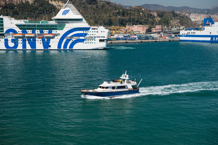 blue vessels: Barcelona, Spain - March 30, 2016: big and small ships or boats marine vessels enter port on blue sea water along beautiful green coast on natural background Editorial