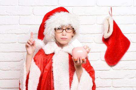 young cute santa claus boy with glasses in red sweater and new year hat with decorative christmas or xmas stocking or boot holding pink piggy pig bank with raised finger on white brick wall background