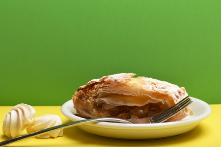 tasty apple strudel pie on white plate near white marshmallows and silver fork on colorful yellow and green background, copy space