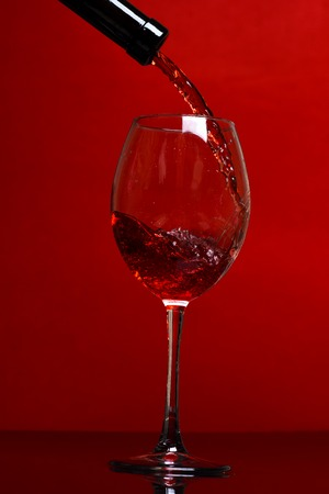 pouring glass with beautifle stream of red wine on red background, side view Stock Photo
