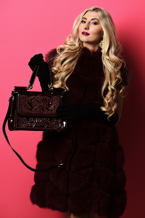 young fashionable sexy pretty woman with beautiful long curly blonde hair in waist coat of burgundy fur and black velvet gloves showing white fashion bag on red studio background