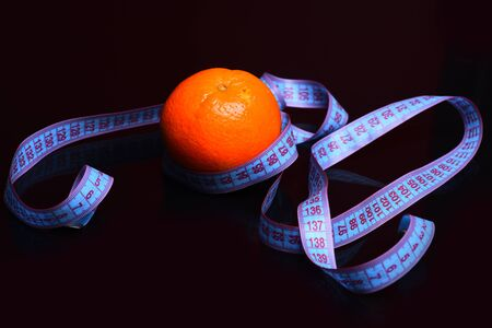 measurement tape: orange with measurement tape around on black background, diet concept Stock Photo