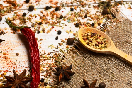 spiciness: set of ingredients for cooking spicy fragrant spices in spoons with cinnamon and chili pepper on net sacking and vintage wooden background, side view