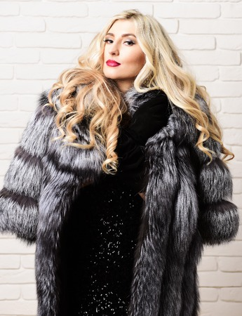 velvet dress: young fashionable sexy pretty rich woman with beautiful long curly blonde hair in waist coat of grey fur and black velvet gloves on brick wall studio background