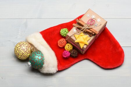 Colorful Christmas or New Year decoration include gift with rose string, yellow bow, cinnamon, Santa Claus red sock, yellow green balls, colorful clews and snowflakes on vintage wooden background