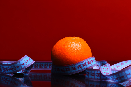 measurement tape: orange with measurement tape around in red background, copy space Stock Photo