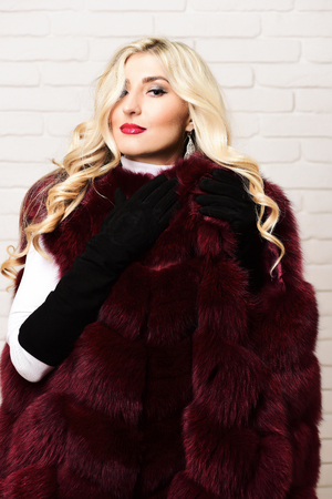 black velvet: young fashionable sexy pretty woman with beautiful long curly blonde hair in waist coat of burgundy or red fur and black velvet gloves on brick wall studio background