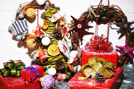 guirnaldas de navidad: set of christmas or new year xmas yellow tree decorative with dry orange, pine cones and red presents or gifts with colorful balls or wreaths on white vintage wooden background