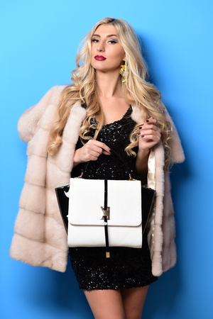 young fashionable sexy pretty woman with beautiful long curly blonde hair in waist coat of beige fur and white black fashion bag in hand on blue studio background