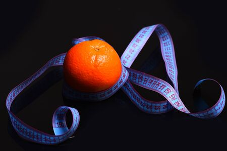 measurement tape: orange with measurement tape around isolated on black background, copy space