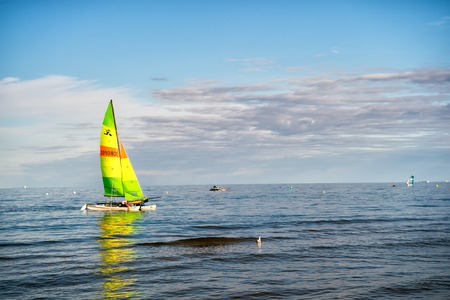 inshore: Gdansk, Poland - September 19, 2016: modern yacht or sailing boat or vessel sails with sailor by wind on sea water waves surface inshore on blue sky