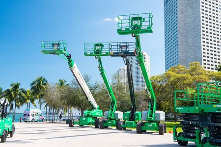 Miami, USA - February 29, 2016: mobile industrial aerial work platforms or equipment with lifts on wheels at exposure or trade show outdoors on sunny day on cityscape Editorial