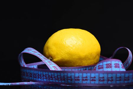 measurement tape: lemon with measurement tape around on black background, copy space
